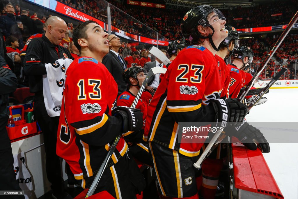 Johnny Gaudreau #13 and Sean Monahan #23 of the Calgary Flames looks at the replay in an NHL game against the St. Louis Blues at the Scotiabank Saddledome on November 13, 2017 in Calgary, Alberta, Canada.