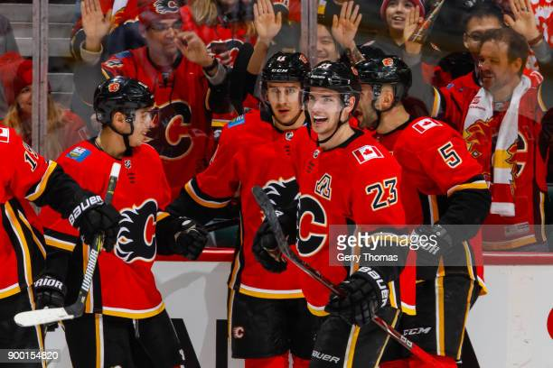 Johnny Gaudreau Mikael Backlund Sean Monahan and Mark Giordano of the Calgary Flames celebrate after scoring the first goal in an NHL game on...