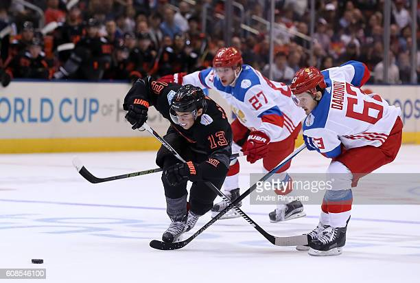 Johnny Gaudreau of Team North America battles for a loose puck with Evgenii Dadonov of Team Russia during the World Cup of Hockey 2016 at Air Canada...