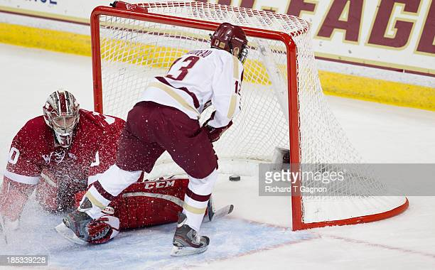 Johnny Gaudreau of the Boston College Eagles slides the puck past Landon Peterson of the University of Wisconsin Badgers for a goal during NCAA...