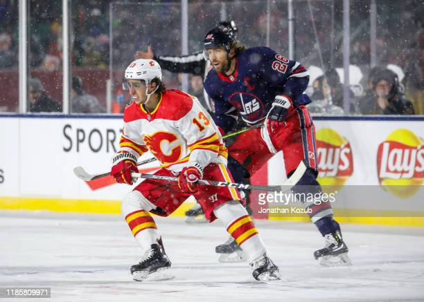 Johnny Gaudreau of the Calgary Flames and Blake Wheeler of the Winnipeg Jets keep an eye on the play during second period action in the 2019 Tim...