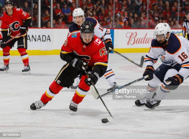 Johnny Gaudreau of the Calgary Flames battles for the puck against Jujhar Khaira of the Edmonton Oilers at Scotiabank Saddledome on March 13 2018 in...