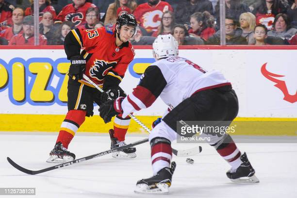 Johnny Gaudreau of the Calgary Flames carries the puck against Jakob Chychrun of the Arizona Coyotes during an NHL game at Scotiabank Saddledome on...
