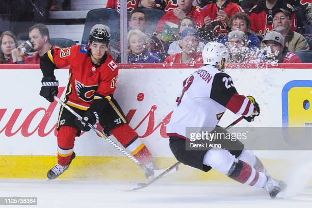 Johnny Gaudreau of the Calgary Flames carries the puck against Oliver EkmanLarsson of the Arizona Coyotes during an NHL game at Scotiabank Saddledome...