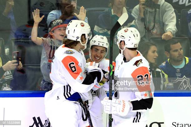 Johnny Gaudreau of the Calgary Flames celebrates with Brock Boeser of the Vancouver Canucks and Oliver EkmanLarsson of the Arizona Coyotes during the...