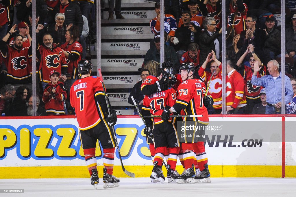 Johnny Gaudreau #13 (C) of the Calgary Flames celebrates with his teammates after scoring against the Edmonton Oilers during an NHL game at Scotiabank Saddledome on March 13, 2018 in Calgary, Alberta, Canada.