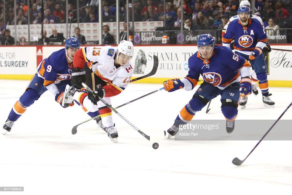 Johnny Gaudreau #13 of the Calgary Flames fights for the puck against Casey Cizikas #53 of the New York Islanders in the third period during their game at Barclays Center on February 11, 2018 in the Brooklyn borough of New York City.