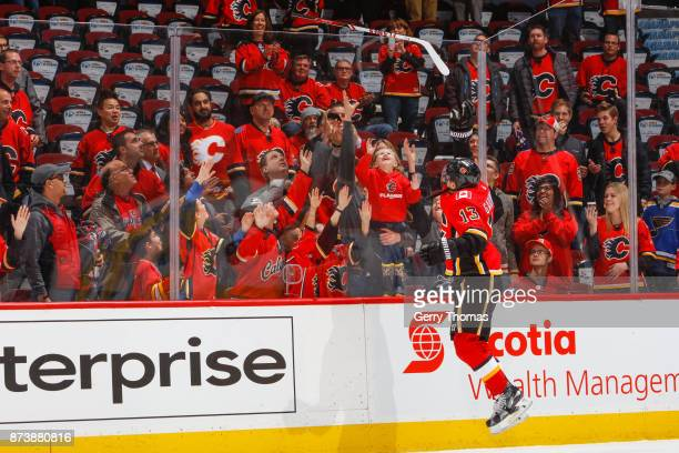 Johnny Gaudreau of the Calgary Flames gives away his stick in an NHL game against the St Louis Blues at the Scotiabank Saddledome on November 13 2017...
