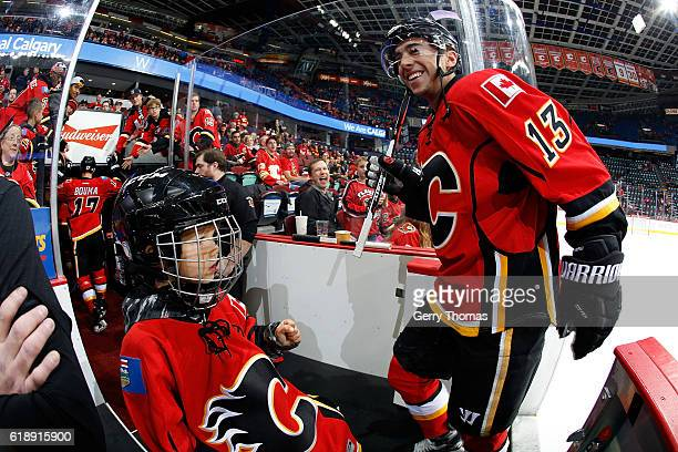 Johnny Gaudreau of the Calgary Flames greets a young fan before an NHL game againsth the Ottawa Senators on October 28 2016 at the Scotiabank...
