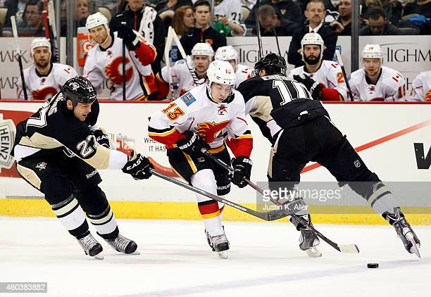 Johnny Gaudreau of the Calgary Flames handles the puck between Craig Adams of the Pittsburgh Penguins and Christian Ehrhoff in the second period...