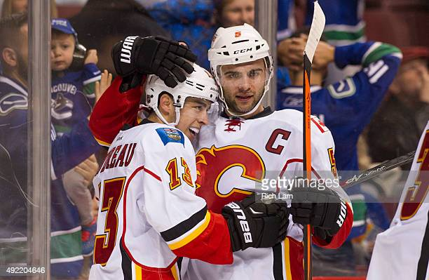 Johnny Gaudreau of the Calgary Flames is congratulated by Mark Giordano after scoring the game winning goal in overtime against the Vancouver Canucks...