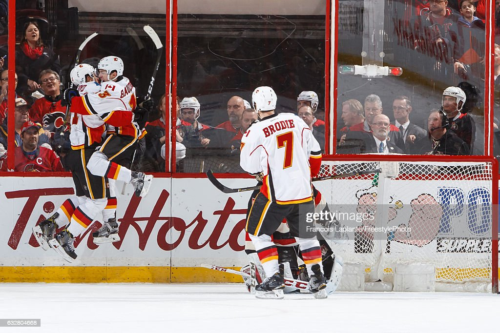 Johnny Gaudreau #13 of the Calgary Flames jumps in the air as he celebrates his overtime winning goal with Mikael Backlund #11 during an NHL game against the Ottawa Senators at Canadian Tire Centre on January 26, 2017 in Ottawa, Ontario, Canada.
