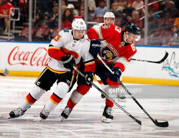 Johnny Gaudreau of the Calgary Flames skates for possession against Evgeni Dadonov of the Florida Panthers at the BBT Center on January 12 2018 in...