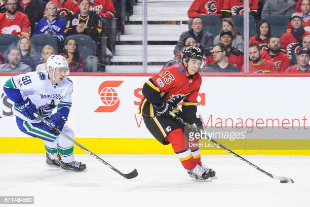 Johnny Gaudreau of the Calgary Flames skates with the puck past Brendan Gaunce of the Vancouver Canucks during an NHL game at Scotiabank Saddledome...