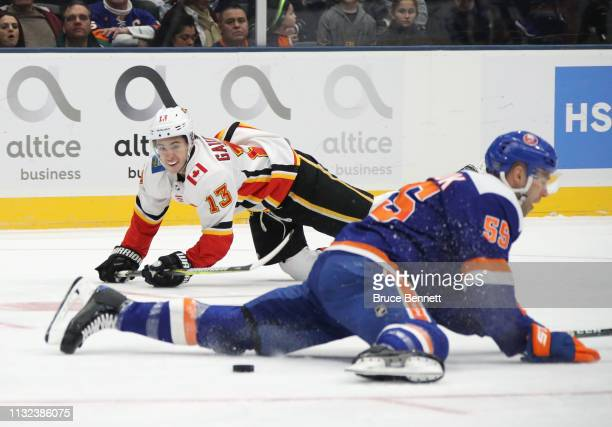 Johnny Gaudreau of the Calgary Flames slips a pass under Johnny Boychuk of the New York Islanders during the first period at NYCB Live's Nassau...