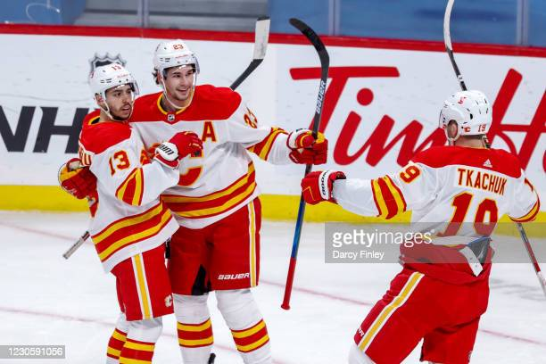 Johnny Gaudreau, Sean Monahan and Matthew Tkachuk of the Calgary Flames celebrate a first period goal against the Winnipeg Jets at the Bell MTS Place...