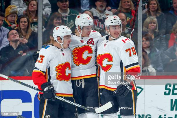 Johnny Gaudreau Sean Monahan and Micheal Ferland of the Calgary Flames celebrate after scoring a goal against the Minnesota Wild during the game at...