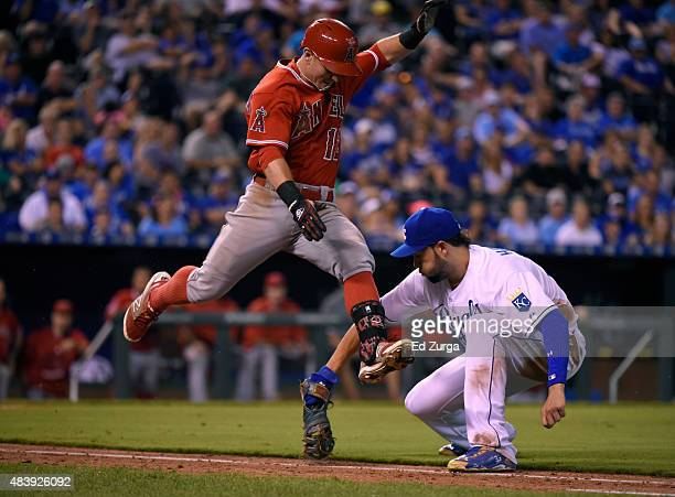 Johnny Giavotella of the Los Angeles Angels of Anaheim leaps past Eric Hosmer of the Kansas City Royals as he heads to first on a bunt single in the...