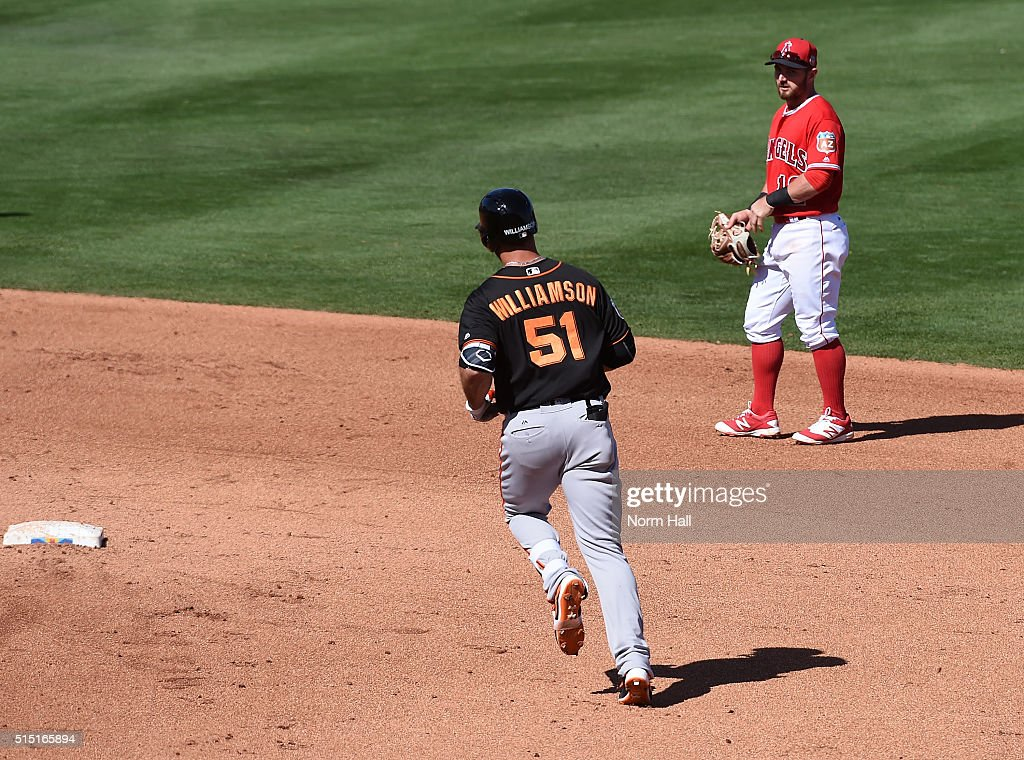Johnny Giavotella #12 of the Los Angeles Angels of Anaheim watches Mac Williamson #51 of the San Francisco Giants round second base after hitting a two run home run during the fifth inning at Tempe Diablo Stadium on March 12, 2016 in Tempe, Arizona.