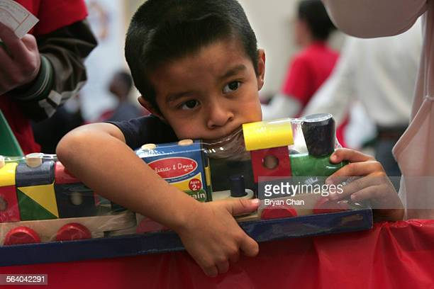 Johnny Guerrero clutches a toy train set he received for Christmas at the Union Rescue Mission's annual 'Christmas Store' which provides more than...