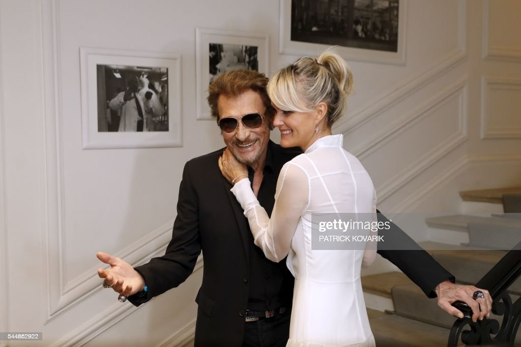 Johnny Hallyday and his wife Laeticia pose before Christian Dior 2016-2017 fall/winter Haute Couture collection fashion show on July 4, 2016 in Paris. /