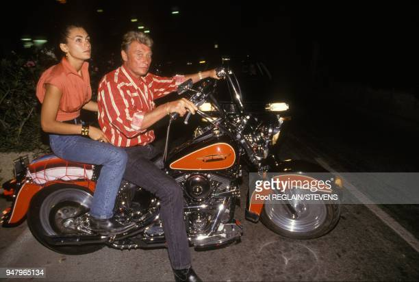 Johnny Hallyday and wife Adeline Blondieau riding Harley Davidson on July 16 1990