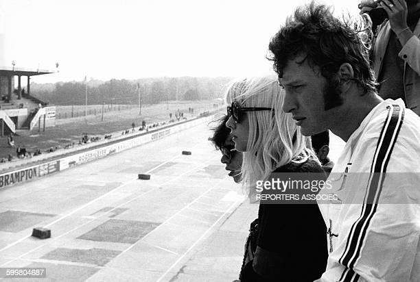 Johnny Hallyday en tenue de course et Sylvie Vartan après une course automobile à bord d'une Ford Mustang sur le circuit de Monthléry circa 1960 à...