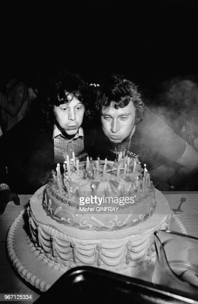 Johnny Hallyday fête son 33ème anniversaire Il souffle les bougies de son gateau avec Gérard Lenorman le 16 juin 1976 à Thoiry France