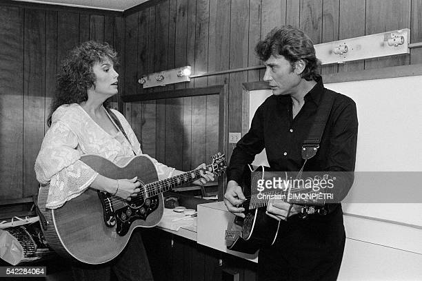 Johnny Hallyday playing with American singer and songwriter Emmylou Harris