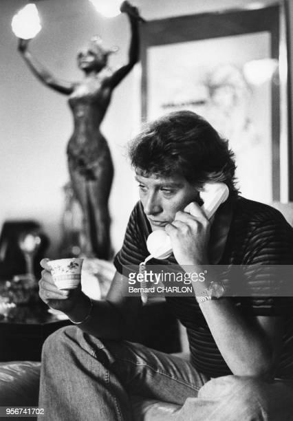 Johnny Hallyday téléphonant avec une tasse de café à la main en septembre 1976 à Paris, France.