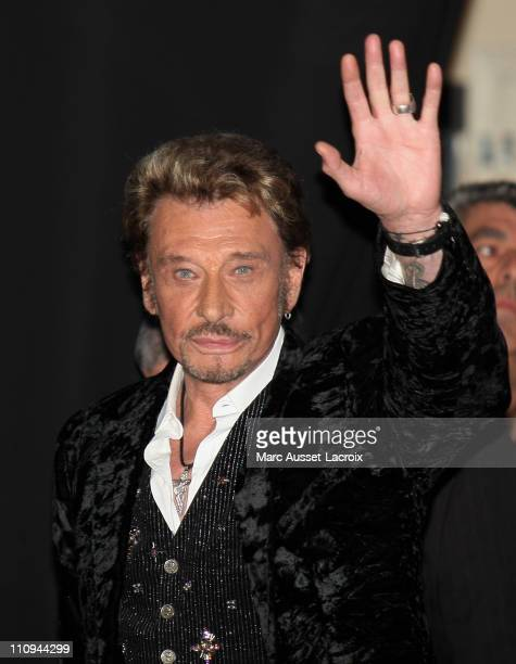 Johnny Hallyday waves to his fans during his new album launch celebration at the Virgin Megastore ChampsElysees on March 27 2011 in Paris France