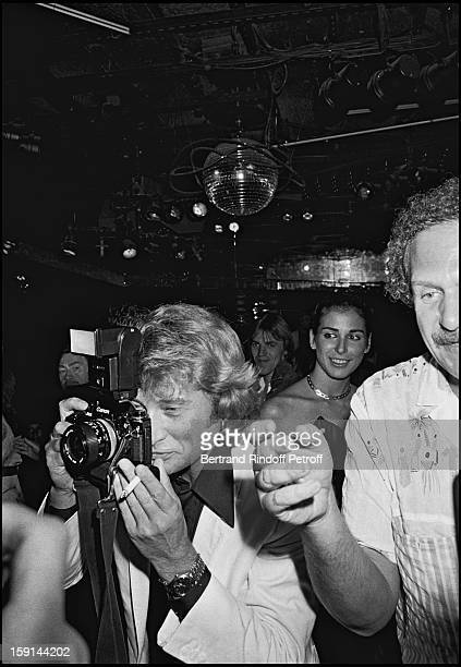 Johnny Hallyday with Mort Schuman takes a photo as he celebrates his 38th birthday at the Elysee Matignon night club in Paris in 1981