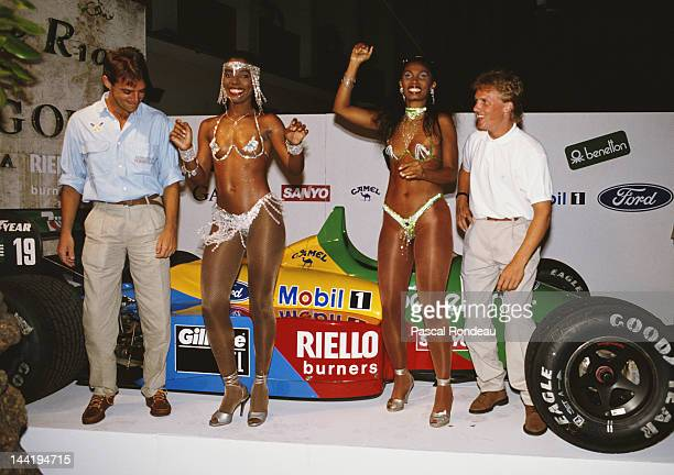 Johnny Herbert of Great Britain and driver the Benetton Formula Benetton B188 Ford V8 stands with two samba dancers and his team mate Alessandro...