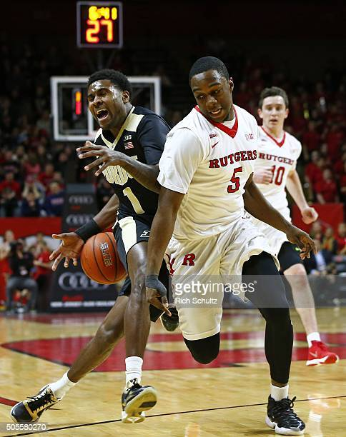 Johnny Hill of the Purdue Boilermakers fights off Mike Williams of the Rutgers Scarlet Knights as he moves the ball up court during the first half of...