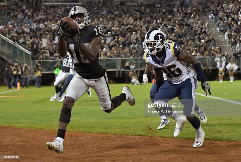 Johnny Holton #16 of the Oakland Raiders catches a seventeen yard touchdown pass over Aaron Green #36 of the Los Angeles Rams during the fourth quarter of their preseason NFL football game at Oakland-Alameda County Coliseum on August 19, 2017 in Oakland, California. The Ram won the game 24-21.