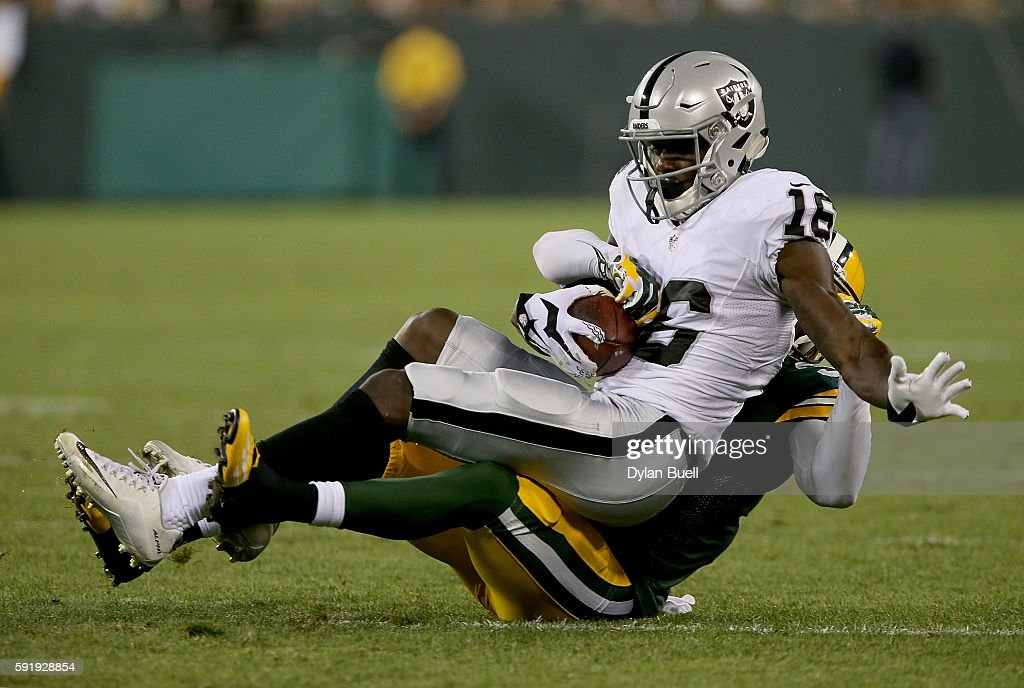 Johnny Holton #16 of the Oakland Raiders is tackled by Robertson Daniel #31 of the Green Bay Packers in the third quarter of a preseason game at Lambeau Field on August 18, 2016 in Green Bay, Wisconsin.
