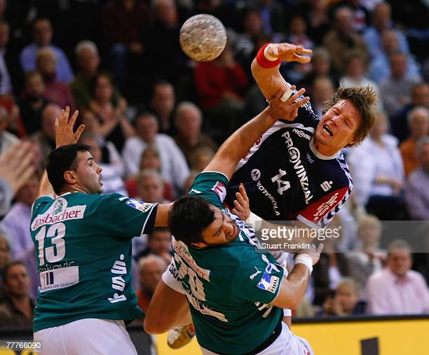 Johnny Jensen of Flensburg is challenged by Kreso Ivankovic and Giorgos Chalkidis of Wetzlar during the Bundesliga Handball game between SG...