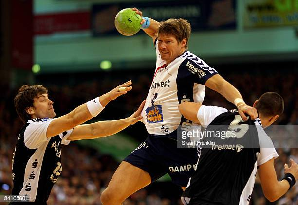 Johnny Jensen of Flensburg is challenged by Marcus Ahlm and Kim Andersson of Kiel during the Toyota Handball league game between SG...