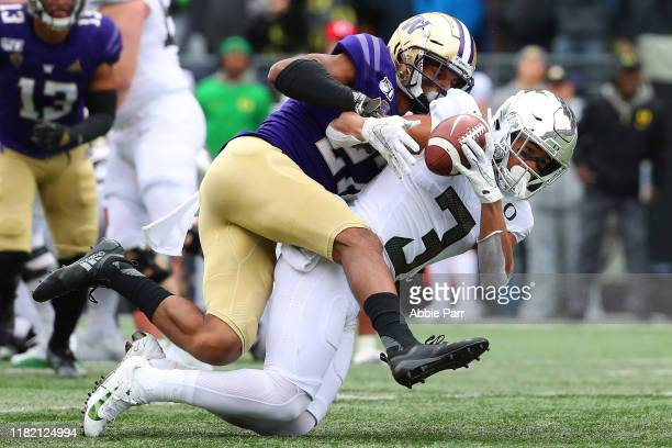 Johnny Johnson III of the Oregon Ducks completes a pass against Keith Taylor of the Washington Huskies in the second quarter during their game at...