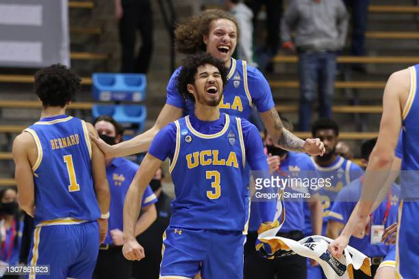 Johnny Juzang of the UCLA Bruins and Mac Etienne celebrate with teammates after defeating the Michigan State Spartans in the First Four game prior to...