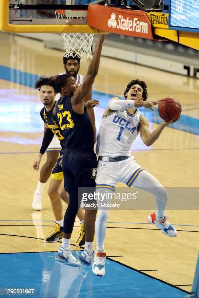 Johnny Juzang of the UCLA Bruins drives to the basket against Jamal Cain of the Marquette Golden Eagles during the first half at UCLA Pauley Pavilion...