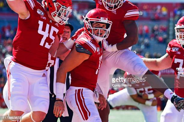 Johnny Langan of the Rutgers Scarlet Knights is lauded by teammates Brandon Myers and Isaih Pacheco of the Rutgers Scarlet Knights for his rushing...