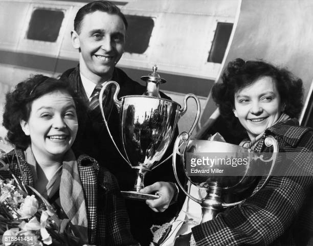 Johnny Leach winner of the men's world table tennis championships arrives at London Airport from Vienna with twins Rosalind and Diane Rowe winners of...