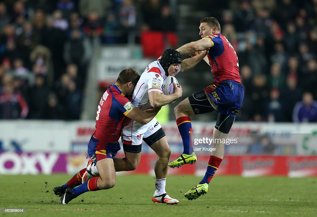 Johnny Lomax of St Helens crashes into Ben Pomeroy and Gregory Mounis of Catalans Dragons during the First Utility Super League match between St Helens and Catalans Dragons at Langtree Park on February 6, 2015 in St Helens, England.
