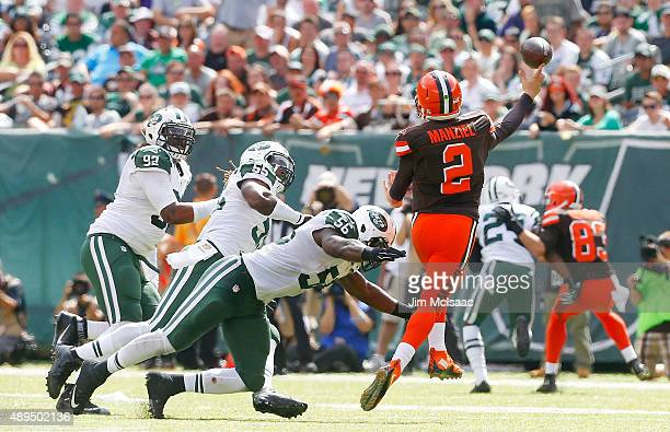 Johnny Manziel of the Cleveland Browns throws a pass under pressure from Kevin Vickerson Lorenzo Mauldin and Demario Davis of the New York Jets at...
