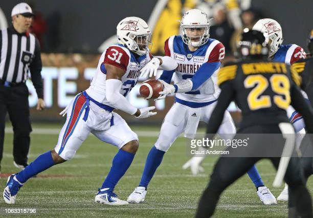 Johnny Manziel of the Montreal Alouettes hands the ball to teammate William Stanback against the Hamilton TigerCats in a CFL game at Tim Hortons...