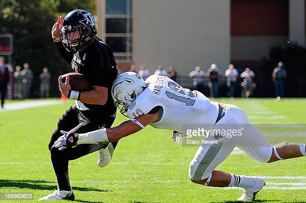 Johnny Manziel of the Texas AM Aggies avoids a tackle by Cameron Lawrence of the Mississippi State Bulldogs at Wade Davis Stadium on November 3 2012...