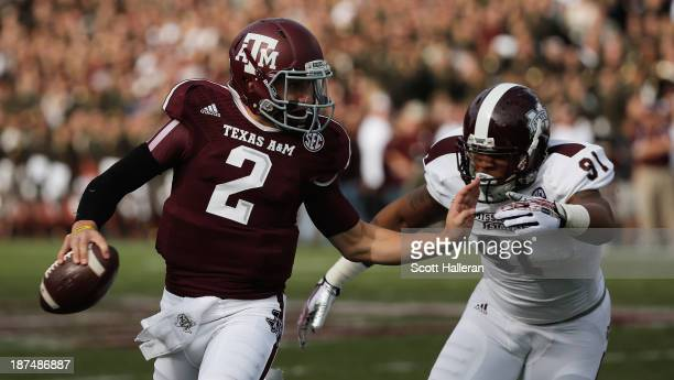Johnny Manziel of the Texas AM Aggies fights off the tackle of Preston Smith of the Mississippi State Bulldogs at Kyle Field on November 9 2013 in...
