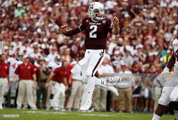 Johnny Manziel of the Texas AM Aggies jumps after throwing a first quarter touchdown during a game against the Alabama Crimson Tide at Kyle Field on...