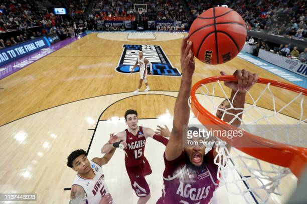 Johnny MCCants of the New Mexico State Aggies dunks the ball against Chuma Okeke of the Auburn Tigers during the second half in the first round of...
